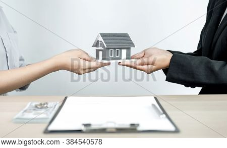 Home Model In Hand A Real Estate Agent And Agent Explain The Business Contract, Rent, Buy, Mortgage,