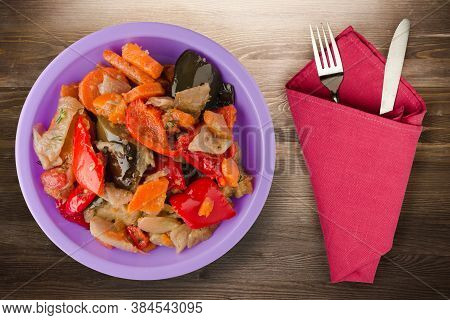 Vegetable Stew On Brown Wooden Background. Stew In Bulgarian On Purple Plate With Top Fork And Knife