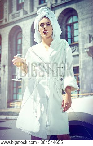 Stunning woman in a white terry dressing gown with a white towel on her head alluring on a city street with a glass of wine and cigarette. Fashion shot.
