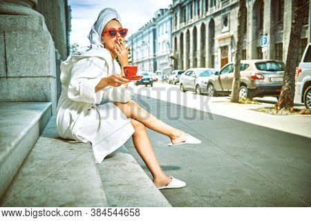 Glamorous lifestyle. Stunning woman in a white terry dressing gown with a white towel on her head and elegant sunglasses alluring on a city street with a cup of tea and cigarette. Fashion shot.