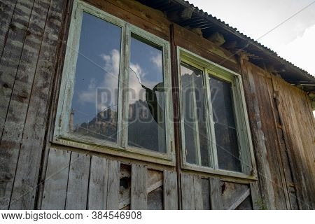 Window With Broken Glass In Old Building. Wooden Window Frame With Partially Broken Glass In Old Aba
