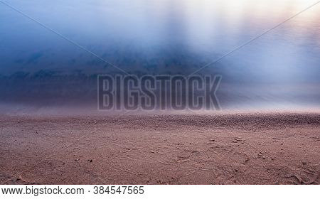 Sand On The Lake Beach With Smooth Tranquil Calm Water Surface Under Soft Sunset Light In Twilight P