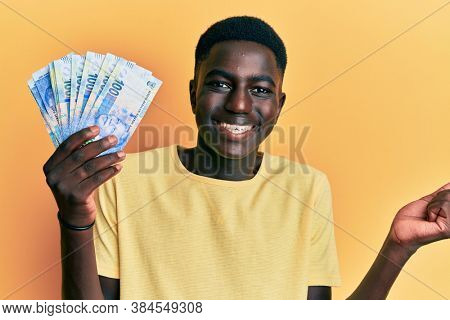Young african american man holding south african rand banknotes screaming proud, celebrating victory and success very excited with raised arm