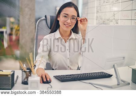 Pleased Young Female Touching Her Stylish Glasses