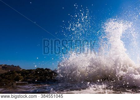 A surge of surf waves on a rocky shore