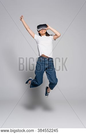 Young Asian Woman In White T-shirt, Jeans And Gumshoes Jumping With Raised Hand While Using Vr Heads