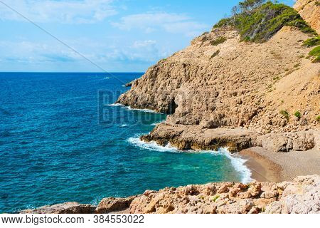 a view over the Llop Mari beach and the Llop Mari sea cave in Hospitalet del Infant, Spain, in the Costa Dorada coast