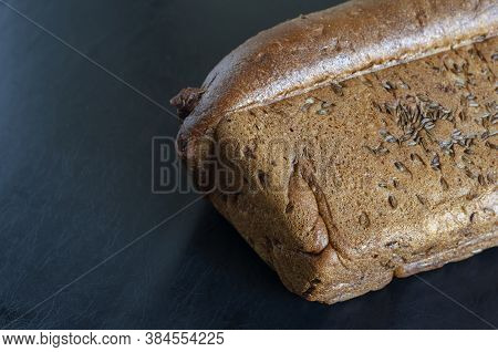 Loaf Of Rye Bread With Caraway Seeds On A Black Background. Side View Of Freshly Baked Homemade Brea