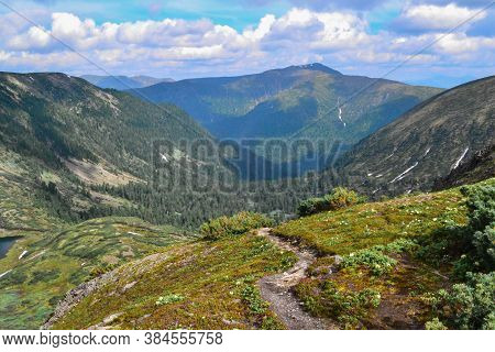 Trail In Blooming Green Meadow With Flowers Among Blue Baikal Mountains  Ridge, Blue Sky, Clouds