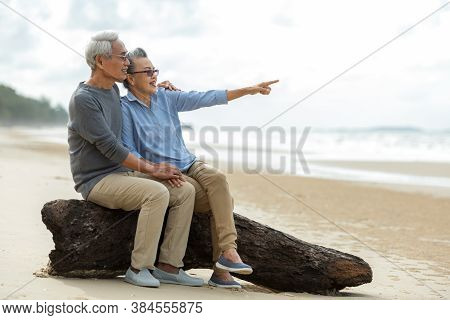 Asian Lifestyle Senior Couple Pointing And Hug See Beach Happy In Love Romantic And Relax Time.  Tou