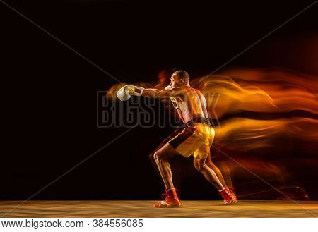 Speed. Professional Boxer Training Isolated On Black Studio Background In Mixed Light. Man In Gloves