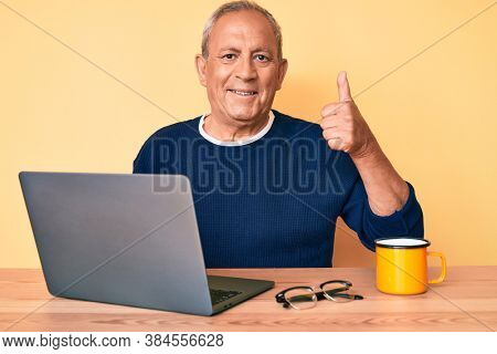 Senior handsome man with gray hair working at the office with laptop smiling happy and positive, thumb up doing excellent and approval sign