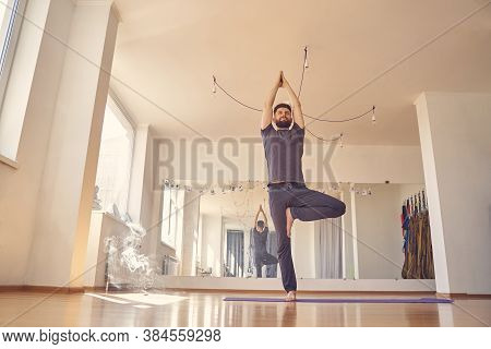 Smiling Young Man Doing Yoga Tree Pose