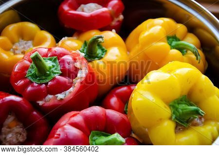 Close-up Red And Yellow Bell Peppers Stuffed With Meat In A Saucepan. Stuffed Peppers With Minced Me