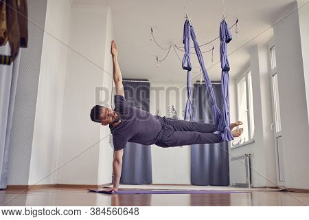 Handsome Athletic Man Doing Aerial Yoga Exercise