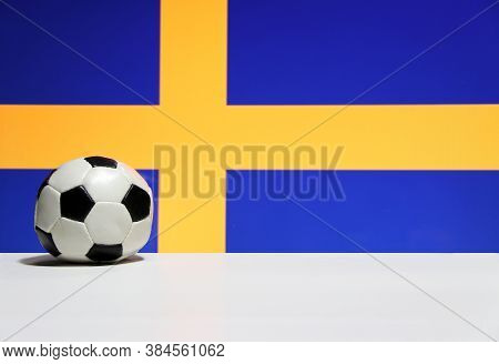 Small Football On The White Floor With Blue And Yelow Color Of Swedish Nation Flag Background. The C