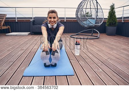 Cheerful Young Woman Doing Exercise On Rooftop Terrace