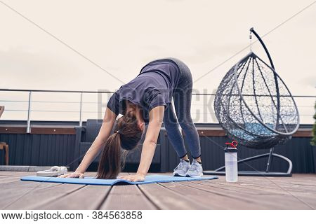 Sporty Young Woman Practicing Yoga On Rooftop Terrace