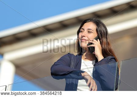 Apartment Renter Calling On Phone In A Balcony Looking Away