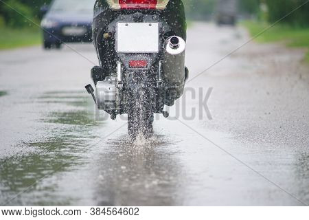 Motorcycle Moped Rides Through A Puddle On A Wet Road In The Rain. Spray Is Flying From The Wheels.