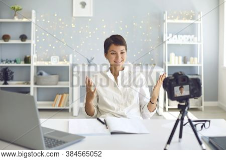 Cheerful Female Vlogger Recording A Video On Camera Sitting At Her Desk In Home Office