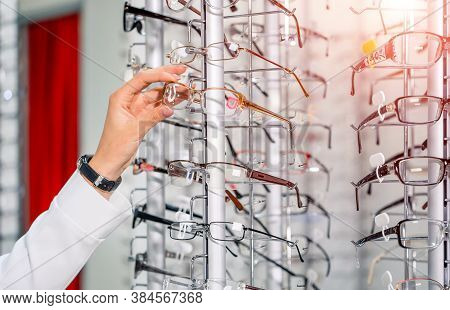 Showcase With Spectacles In Modern Ophthalmic Store. Hands With Glasses. Row Of Glasses At An Optici