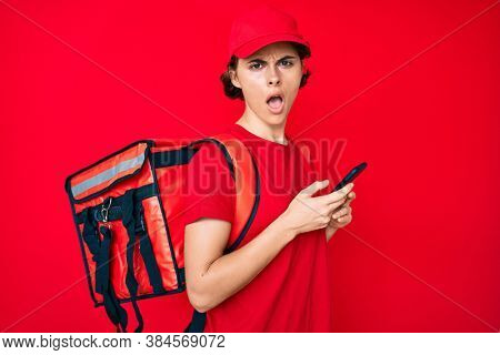 Young hispanic woman holding delivery box calling assistance in shock face, looking skeptical and sarcastic, surprised with open mouth