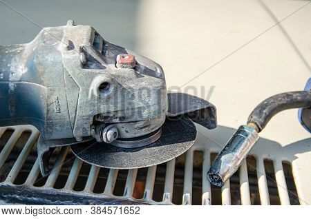 Sawing A Weld Seam On Iron Corners With An Angle Grinder With Selective Focus On Flying Sparks. The