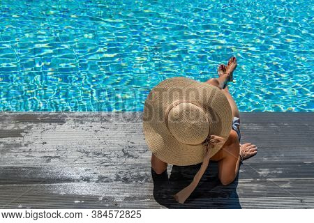 Woman sitting on the deck at the swimming pool