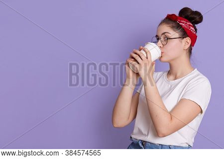 Brunette Female Holds And Drinks Coffee To Go, Enjoys Pleasant Drink, Wears White Casual T Shirt And