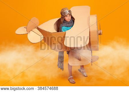 Cute dreamer girl playing with a cardboard airplane. Childhood. Fantasy, imagination. Studio portrait on a yellow background.
