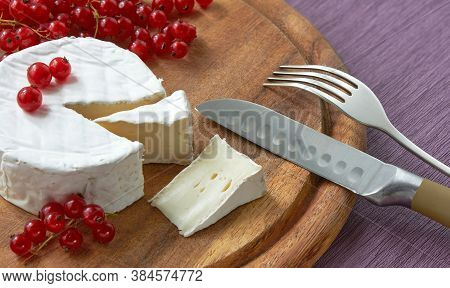Fresh French Brie Cheese Under White Mold On A Wooden Board With Red Currant