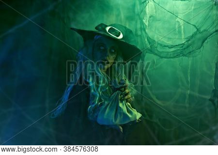 A scary ugly witch stands in an abandoned witch's den. Halloween. Scary tales.