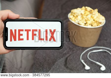 Close Up Mans Hand Holding A Mobile Phone With Netflix Logo With Apple Earphones And Popcorn Box Nex