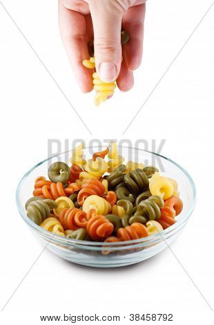 Hand picking Trottole Tricolore from bowl, clipping path