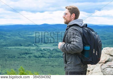 The Guy Stands On The Top Of The Mountain With A Backpack And Enjoys The View.