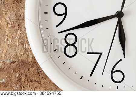 Dinner Time Concept. A Part Of White Round Analog Clock Face Against The Background Of A Red Brick W
