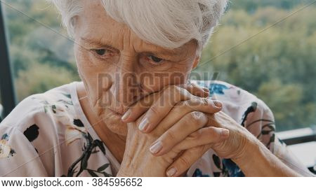 Elderly Caucasian Woman In Nursing Care Home, With Sadness In Her Eyes, Self Isolation Due To The Gl
