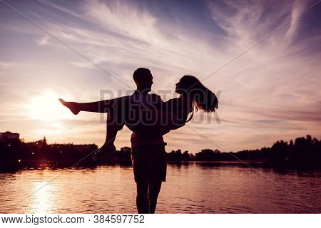 Man Holding Woman In Hands. Couple Having Fun On River Bank At Sunset. Silhouettes Of People