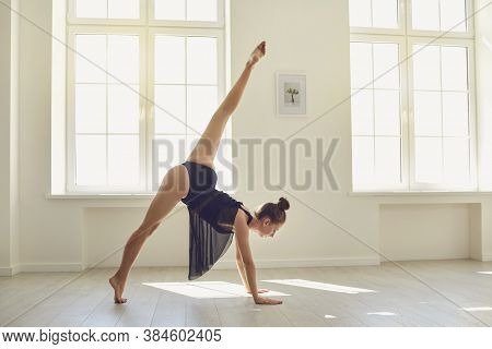 Good Looking Slender Female Gymnast Getting Ready To Do A Handstand In Modern Studio
