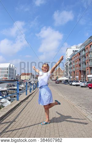 Woman Standing On A City Street Raising Her Hands Up. Happy Woman Rejoicing In Summer In City. Beaut