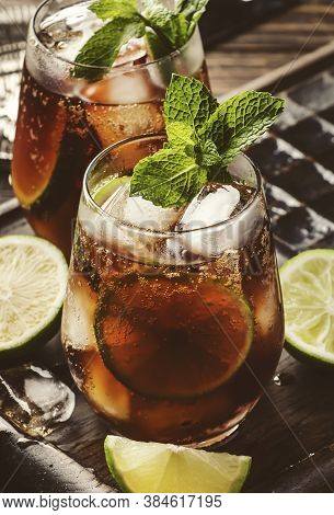Cuba Libre Or Rum Cola Cocktail With Strong Alcohol, Lemon Juice, Lime And Ice, Dark Background, Ste