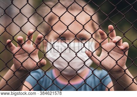 A Child In A Medical Mask Holds The Fence With His Hands. Quarantine Melancholy And Loneliness Conce