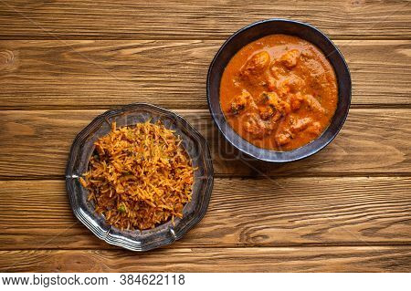 Indian Chicken Curry In Old Metal Bowl And Pilaf With Biryani Rice On Wooden Rustic Background. Trad