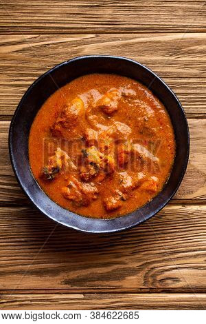 Indian Chicken Curry With Tomato Gravy On Wooden Rustic Background. Traditional Indian Dish Butter C