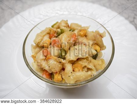 Close Up Of Vegetable Macaroni Cooked In White Sauce Served In A Transparent Bowl Isolated On White