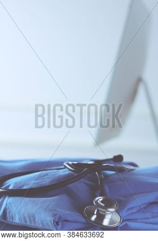 Image of stethoscope and doctor coat on the table in a consultancy room. Medical concept