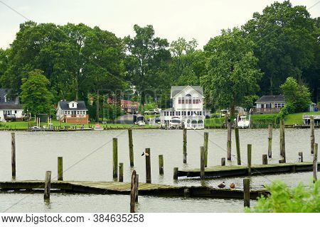 Cobb Island, Maryland, U.s.a - August 15, 2020 - The View Of The Wooden Dock And A Waterfront Home B