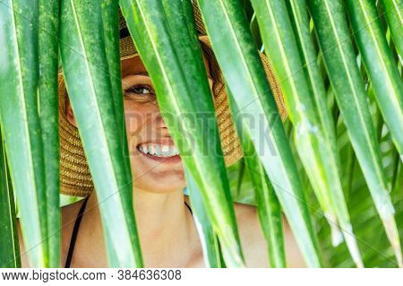 Woman Hiding Behind The Palm Leaves. Vacation Concept