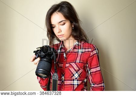 Tired Serious Woman Photographer In Red Shirt Holding Camera And Looking At Bad,failed And Unsuccess